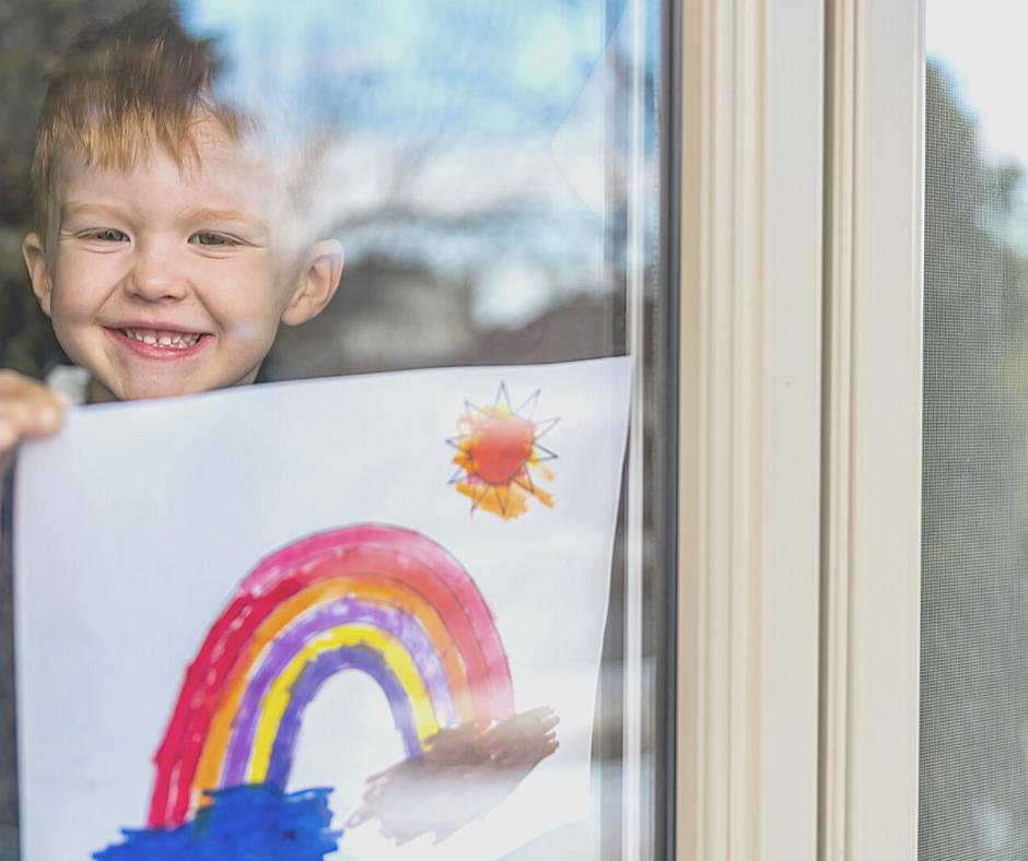 little boy holding rainbow drawing in window